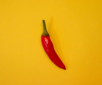 red chili on yellow surface 3194495 1